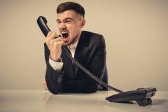 Ο νεαρός άνδρας σχηματίζει το αριθμό τηλεφώνου καθμένος στο γραφείο Στοκ Εικόνες