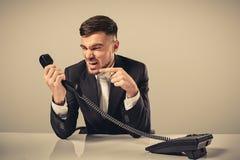 Ο νεαρός άνδρας σχηματίζει το αριθμό τηλεφώνου καθμένος στο γραφείο Στοκ Φωτογραφίες