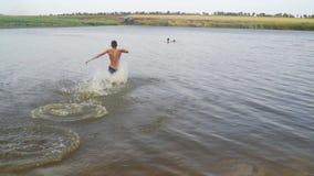Ο νεαρός άνδρας τρέχει στη λίμνη και βουτά απόθεμα βίντεο