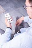 Ο νεαρός άνδρας φαίνεται ένα έξυπνο σπίτι app στο smartphone του Στοκ εικόνες με δικαίωμα ελεύθερης χρήσης