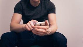 Ο νεαρός άνδρας χρησιμοποιεί το έξυπνο τηλέφωνό του απόθεμα βίντεο