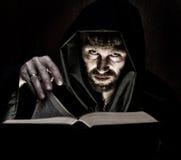 Ο νεκρομάντης πετά τις περιόδους από το παχύ αρχαίο βιβλίο από το φως ιστιοφόρου σε ένα σκοτεινό υπόβαθρο Στοκ εικόνα με δικαίωμα ελεύθερης χρήσης