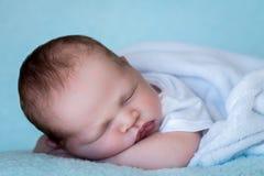 Ο νεογέννητος ύπνος μωρών στα όπλα του κλείνει επάνω Στοκ Εικόνες