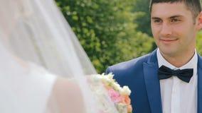 Ο νεόνυμφος δίνει την ανθοδέσμη νυφών των γαμήλιων λουλουδιών κοντά στο παλαιό κάστρο απόθεμα βίντεο