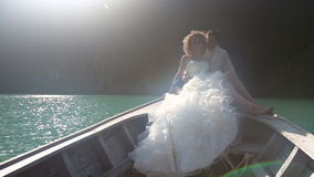 ο νεόνυμφος αγκαλιάζει τη συνεδρίαση νυφών στη βάρκα longtail απόθεμα βίντεο
