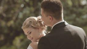 Ο νεόνυμφος αγκαλιάζει το fiancee στεμένος σε ένα πάρκο απόθεμα βίντεο