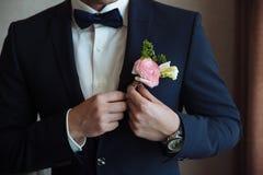 Ο νεόνυμφος βάζει σε μια μπουτονιέρα σε μια ημέρα γάμου σε ένα σακάκι Στοκ εικόνες με δικαίωμα ελεύθερης χρήσης