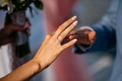 Ο νεόνυμφος βάζει το δαχτυλίδι στο δάχτυλο της νύφης Στοκ φωτογραφία με δικαίωμα ελεύθερης χρήσης