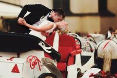 Ο νεόνυμφος κάμπτει τη νύφη πέρα από το κράτημα την στα όπλα του και τη στάση στο τ Στοκ φωτογραφία με δικαίωμα ελεύθερης χρήσης