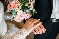 Ο νεόνυμφος και η νύφη κινηματογραφήσεων σε πρώτο πλάνο κρατούν ότι τα χέρια στο ANG ημέρας γάμου παρουσιάζουν δαχτυλίδια Έννοια  Στοκ Εικόνα