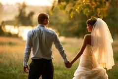Ο νεόνυμφος και η νύφη κρατούν τα χέρια στο πράσινο δάσος υποβάθρου στοκ φωτογραφίες