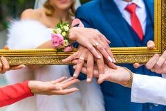 Ο νεόνυμφος και η νύφη παρουσιάζουν δαχτυλίδια τους μέσω του πλαισίου Στοκ φωτογραφία με δικαίωμα ελεύθερης χρήσης