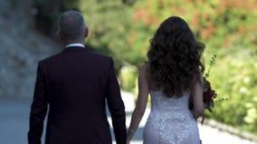 Ο νεόνυμφος και η νύφη περπατούν κατά μήκος των χεριών και του κοιτάγματος εκμετάλλευσης ζεύγους αλεών προς τα εμπρός φιλμ μικρού μήκους