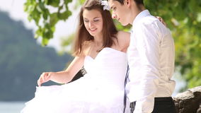 ο νεόνυμφος και η νύφη προσπαθούν να αγκαλιάσουν πιό άνετα απόθεμα βίντεο