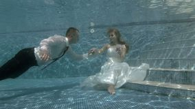 Ο νεόνυμφος κολυμπά υποβρύχιο στη νύφη που κάθεται στο κατώτατο σημείο της λίμνης και φιλά το χέρι της απόθεμα βίντεο