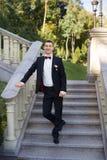 Ο νεόνυμφος κρατά έναν δεσμό και χαμογελά Πορτρέτο του νεόνυμφου στο πάρκο στη ημέρα γάμου τους Οι πλούσιοι καλλωπίζουν στη ημέρα Στοκ φωτογραφία με δικαίωμα ελεύθερης χρήσης