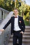 Ο νεόνυμφος κρατά έναν δεσμό και χαμογελά Πορτρέτο του νεόνυμφου στο πάρκο στη ημέρα γάμου τους Οι πλούσιοι καλλωπίζουν στη ημέρα Στοκ Εικόνα