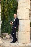 Ο νεόνυμφος κρατά έναν δεσμό και χαμογελά Πορτρέτο του νεόνυμφου στο πάρκο στη ημέρα γάμου τους Οι πλούσιοι καλλωπίζουν στη ημέρα Στοκ Εικόνες