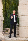 Ο νεόνυμφος κρατά έναν δεσμό και χαμογελά Πορτρέτο του νεόνυμφου στο πάρκο στη ημέρα γάμου τους Οι πλούσιοι καλλωπίζουν στη ημέρα Στοκ Φωτογραφίες