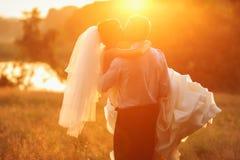 Ο νεόνυμφος κρατά και φιλά τη νύφη του στο υπόβαθρο suset στοκ φωτογραφίες με δικαίωμα ελεύθερης χρήσης