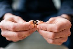 Ο νεόνυμφος κρατά στα χέρια του που δύο γαμήλια δαχτυλίδια, κάθονται και περιμένουν Στοκ εικόνα με δικαίωμα ελεύθερης χρήσης