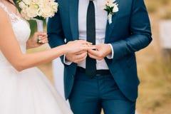 Ο νεόνυμφος ντύνει ένα δαχτυλίδι στο δάχτυλο της νύφης σε έναν γάμο Στοκ Φωτογραφίες