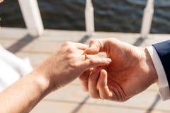 Ο νεόνυμφος ντύνει το δαχτυλίδι αρραβώνων νυφών ` s στο δάχτυλο ευτυχής εκλεκτής ποιότητας γάμος ημέρας ζευγών ιματισμού Στοκ Φωτογραφία