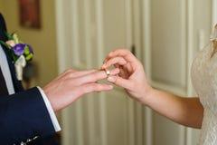 Ο νεόνυμφος νυφών βάζει το δαχτυλίδι σε ετοιμότητα του στη ημέρα γάμου Στοκ Εικόνα