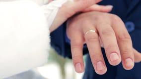 Ο νεόνυμφος νυφών ζευγών κινηματογραφήσεων σε πρώτο πλάνο χεριών κρατά το δαχτυλίδι για φιλμ μικρού μήκους