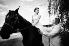 Ο νεόνυμφος οδηγεί το άλογο από το χαλινάρι Η νύφη κάθεται στο saddl στοκ εικόνες με δικαίωμα ελεύθερης χρήσης