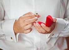Ο νεόνυμφος πήρε τα γαμήλια δαχτυλίδια από την κόκκινη περίπτωση Στοκ φωτογραφία με δικαίωμα ελεύθερης χρήσης