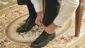 Ο νεόνυμφος που βάζει τα παπούτσια επάνω και τα κορδόνια δεσμών απόθεμα βίντεο