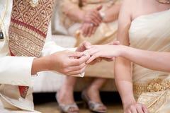 Ο νεόνυμφος που φορά το γαμήλιο δαχτυλίδι για τη νύφη του στοκ εικόνα