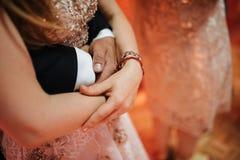 Ο νεόνυμφος σε ένα κοστούμι αγκαλιάζει τη νύφη σε ένα γαμήλιο φόρεμα στοκ φωτογραφία