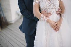 Ο νεόνυμφος σε ένα κοστούμι αγκαλιάζει τη νύφη σε ένα γαμήλιο φόρεμα στοκ εικόνα