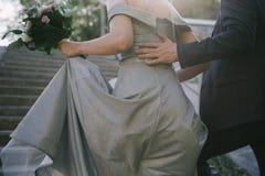 Ο νεόνυμφος σε ένα κοστούμι αγκαλιάζει τη νύφη σε ένα γαμήλιο φόρεμα στοκ εικόνες
