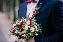 Ο νεόνυμφος σε ένα σκούρο μπλε σακάκι κρατά μια ανθοδέσμη των τριαντάφυλλων Στοκ Φωτογραφία