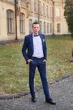 Ο νεόνυμφος σε μια μπλε τοποθέτηση δεσμών κοστουμιών και τόξων στη φωτογραφία Στοκ Φωτογραφίες