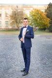 Ο νεόνυμφος σε μια μπλε τοποθέτηση δεσμών κοστουμιών και τόξων στη φωτογραφία Στοκ Εικόνες