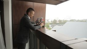 Ο νεόνυμφος στέκεται στο μπαλκόνι με μια ανθοδέσμη στα χέρια του απόθεμα βίντεο
