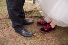 Ο νεόνυμφος στο παντελόνι και τα μαύρα παπούτσια και η νύφη στα κόκκινα πάνινα παπούτσια που παρουσιάζουν γαμήλια παπούτσια τους Στοκ Εικόνες