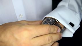 Ο νεόνυμφος στο πουκάμισο ρυθμίζει το ρολόι δίνει προσοχή στη χρονική κινηματογράφηση σε πρώτο πλάνο απόθεμα βίντεο