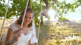 Ο νεόνυμφος τινάζει τη νύφη του στην ταλάντευση και χαμογελά με την αγάπη κοιτάζει Η γυναίκα και ο άνδρας στη ρομαντική συνεδρίασ φιλμ μικρού μήκους