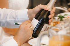 Ο νεόνυμφος υπογράφει ένα μπουκάλι της σαμπάνιας στοκ εικόνα με δικαίωμα ελεύθερης χρήσης