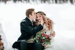 Ο νεόνυμφος φιλά τη νύφη του στο ναό στο άσπρο υπόβαθρο χιονιού _ Εκλεκτική εστίαση στην ανθοδέσμη στοκ εικόνες