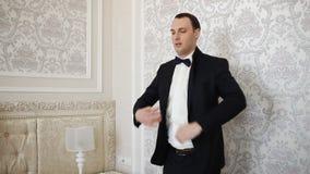 Ο νεόνυμφος φορά ένα κοστούμι στο εσωτερικό Αρσενικό πορτρέτο του όμορφου τύπου απόθεμα βίντεο