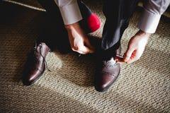 Ο νεόνυμφος φορά τα μαύρα παπούτσια στο ξενοδοχείο Στοκ φωτογραφίες με δικαίωμα ελεύθερης χρήσης