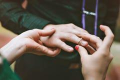 Ο νεόνυμφος φορά τη νύφη δαχτυλιδιών Μια γυναίκα φορά ένα δαχτυλίδι στον άνδρα δέσμευση Στοκ φωτογραφία με δικαίωμα ελεύθερης χρήσης