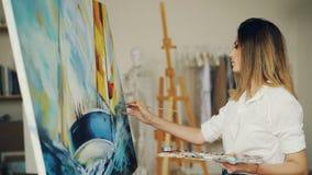 Ο ξανθός ζωγράφος κοριτσιών εργάζεται στο στούντιο απεικονίζοντας το τοπίο και τη βάρκα θάλασσας στον καμβά χρησιμοποιώντας τα χρ απόθεμα βίντεο