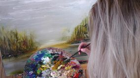Ο ξανθός καλλιτέχνης χρωματίζει τα ελαιοχρώματα στον καμβά Λεπτομέρειες, μπροστινή άποψη απόθεμα βίντεο